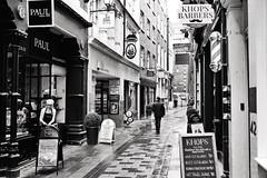 Cut Through (Douguerreotype) Tags: uk gb britain british england london city urban bw blackandwhite mono monochrome street people candid shop cafe barber alley lane sign