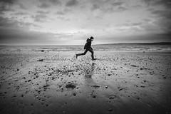 leg it (james_drury) Tags: uk winter boy sea sky cold beach mono blackwhite seaside yorkshire stormy running run pebble dash shore figure lone desolate pebbly filey brigg explored canonef24105mmf4lisusm jamesdrury