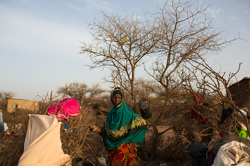 An elderly woman stands in front of her kitchen in Waryuguleh woreda