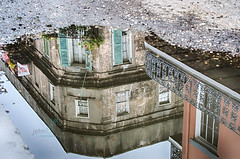 Reflection into New Orleans (Dr_Fu_Manchu) Tags: street new old reflection john french puddle j nikon orleans louisiana cityscape d decay balcony miller shutters quarter curb vieuxcarre d7000 johnjmiller