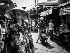 Saigon 18 (arsamie) Tags: saigon vietnam ho chi minh tanh binh market cho ba old woman flowers hat triangle conical non la asia black white monochrome life people candid hai trung street suspicious angry