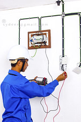 wireman during testing work (sydeen) Tags: blue test white lamp wall work switch miniature uniform wiring board main nail helmet hard cable testing system safety wires installation electricity isolation meter manual collar electrical circuit install protection lead materials tester breaker distribution holder workman electrician prob installing skilled