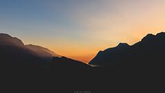 Burning horizon (Nicola Pezzoli) Tags: italy lake garda lago riva trentino nature arco castle sunset mountain silhouette water horizon sky clouds light rays