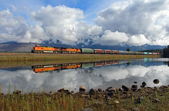 High country reflection (Moffat Road) Tags: railroad reflection water clouds creek train montana rocks day mt cloudy frogpond trout ge tranquil lowclouds bnsf mrl freighttrain dash9 c449w montanaraillink heritageii manifestfreight woodchipcars vision:beach=089 vision:mountain=059 mrlsfourthsubdivision