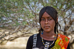 Afar girl near Semera, Ethiopia (NeSlaB .) Tags: poverty africa travel decorations portrait woman colors girl beauty look youth canon hair photo necklace eyes women village dress desert traditional country young culture photojournalism tribal clothes ornaments braids tradition ethiopia tribe ethnic society hairstyle developingcountries reportage nationalgeographic ethnography ethnology afar etiopia braiding danakil ethnies semera hafar neslab davidecomelli vision:people=099 vision:face=099 vision:outdoor=0894 hafari