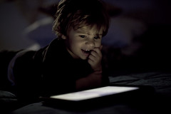 Portrait of a small boy using a tablet (Nasos Zovoilis) Tags: life city blue boy portrait brown white playing reflection cute love home apple beautiful face childhood closeup fun toy happy kid bed eyes hands toddler europe alone child play hand looking little sweet head expression background room small joy young adorable handsome son athens read greece jeans sofa health blond attractive casual worry inside charming care tablet hold ipad