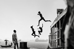 An Urban Childhood... (_MaK_) Tags: street childhood decisive people monochrome moment jump river bath urban rain boat bw bangladesh candid
