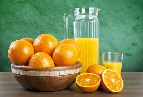 orange juice with oranges on wooden table