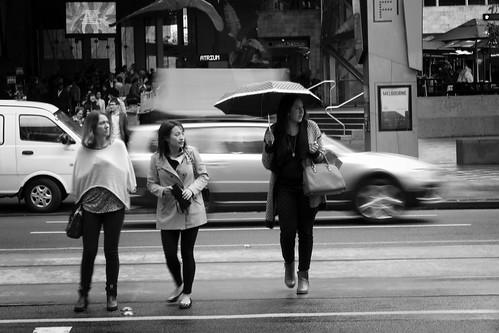road street ladies people motion wet lines rain umbrella square women pretty crossing slow candid tracks streetphotography tram australia melbourne blurred poncho flinders federation careful watchful stphotographia ta260159