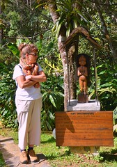 A folded arms tourist checks out the Kalanoros wooden carving and the mystery of the Kalanoros Tribe, at Vakona Forest Lodge, East  Madagascar. (One more