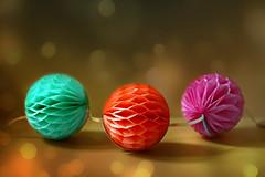 Honeycomb Balls (Through Serena's Lens) Tags: 52stilllifes round honeycombballs bokeh stilllife dof garland paper tabletop green orange pink color colorful