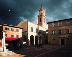 Pienza in Storm Light (Philipp Klinger Photography) Tags: italien houses windows light shadow sky italy sun house storm bird clock church window birds architecture dark fly flying nikon italia angle bright wide wideangle stormy medieval clocktower tuscany piazza pienza toscana palazzo renaissance oiseaux darksky d800 toska