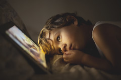 Small boy looking a tablet in the dark (Nasos Zovoilis) Tags: life city blue boy portrait brown white playing reflection cute love home apple beautiful face childhood closeup dark fun toy happy kid bed eyes hands toddler europe alone child play hand looking little sweet head expression background room small joy young adorable handsome son athens read greece sofa health blond attractive casual worry inside charming care tablet hold ipad
