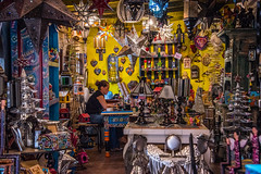 2016 - Mexico - San Miguel de Allende - Busy (Ted's photos - For Me & You) Tags: 2016 guanajuato mexico nikon nikond750 nikonfx sanmigueldeallende tedmcgrath tedsphotos tedsphotosmexico cropped vignetting shop female desk crowded busy art lamps desks catrinas birdhouse junk vendor store