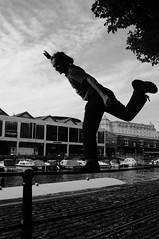 Hermes, messenger of the gods (pix-4-2-day) Tags: man railing geländer balance bancieren balancing act balanceakt bristol harbour bazaar boat boot wasser water black white schwarzweis himmel sky clouds wolken baum tree hermes messenger pix42day