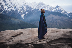 young girl staying on a large rock in the Himalayan mountains among snow peaks (Zhenya bakanovaAlex Grabchilev) Tags: blue winter wild portrait people india mountain snow mountains travelling female landscape women view outdoor wildlife indian young peak silence yogi meditation wilderness himalaya range vashisht