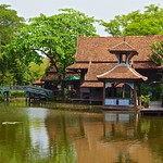 Lake with trees and houses in The Ancient City - Mueang Boran in Samut Phrakhan near Bangkok, Thailand thumbnail
