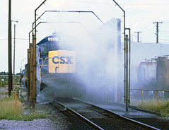 CSX locomotives led by GE B30-7 # 5551, are seen entering the high pressure spray washer in the Uceta Railroad Yard at Tampa, Florida, 1989 1 of 11 (alcomike43) Tags: old railroad color classic water yard vintage ties photo diesel tracks engine slide trains spray historic photograph rails locomotive freighttrains ge ballast generalelectric rightofway csx dieselengine 5551 tampaflorida railroadyard roadbed diesellocomotive cleaningequipment dieselelectriclocomotive b307 ucetarailroadyard locomotivewasher highpressurewaterjetwasher
