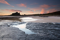 2 Bamburgh Castle, Northumberland (keithpurchese) Tags: orange water clouds sunrise sand northumberland slate stillness newday bamburghcastle castleblackandwhite