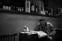 Hat helps the concentration (Giulio Magnifico) Tags: life old inspiration news man hat composition dark beard lights newspaper intense alone emotion wine reader expression candid character dream citylife elder aged osteria udine nikond800e sigma35mmf14dghsm