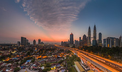 Kuala Lumpur City: Morning Rays (Hafidz Abdul Kadir) Tags: street new travel blue light sunset red vacation sky urban panorama cloud sun motion blur tower yellow skyline architecture night speed skyscraper sunrise canon buildings landscape outdoors photography corporate lights evening town twilight construction highway scenery asia downtown cityscape view traffic contemporary transport magenta landmark aerial illuminated east business commercial transportation malaysia slowshutter getty wa destination 5d metropolis tall bluehour kuala kualalumpur financial metropolitan goldenhour scapes gettyimages twop 1740f4 greatphotographers 5dmark2