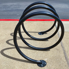 Loopy (bill barfield) Tags: spiral loops bicyclerack red houston sidewalk parkinglot pavement asphalt cement concrete shadow linescurves