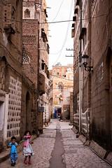 Sana'a, Yemen (Rod Waddington) Tags: yemen yemeni middle east streetphotography sanaa city children two old architecture street streetphoto paving towerhouses streetlight people outdoor outdoors outside traditional tribal islam islamic unesco
