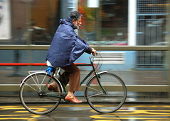 A cape against the rain (jeremyhughes) Tags: street city urban motion wet water rain bike bicycle speed cycling movement nikon edinburgh cyclist riding rainy cape nikkor raining panning rider fenders allweather raincape d40 18200mmf3556gvr