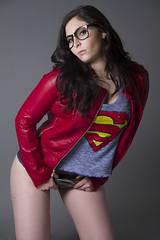Brunette in superman tshirt finger fucks herself on the sofa