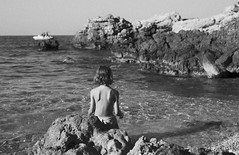 on the rocks by the sea (gorbot.) Tags: sea summer blackandwhite beach girl naturereserve sicily canoneos5d riservanaturaledellozingaro nikonfmount silverefex carlzeisszf50mmplanarf14