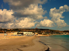 The beach of Mellieha, Malta (STEHOUWER AND RECIO) Tags: camera red sea vacation sky people holiday tower beach architecture clouds composition photography coast photo sand aqua image tag tags malta coastline popular redtower mellieha sunbeds populartags mediterennean