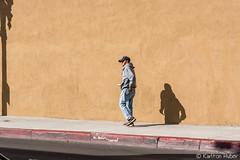 Santa Ana - Man, Multitasking (www.karltonhuberphotography.com) Tags: 2017 buildingside citystreets color karltonhuber lookingleft male man orangecountycalifornia profile santaanacalifornia shadow sidelight sidewalk southerncalifornia streetphotography streetscene theoc urban walking