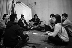 playing oud (dominic_wenger) Tags: grã¼n greece sindos thessaloniki athen frakapor refugee refugees refugeecamp camp military crysis borders open world problem swisscross volunter help portrait face family poor man woman kids chil child children beautiful beauty war syria tent tents hall light dark cold black blackandwhite blackwhite people human humanity sun boring life flee volunteer teen teens teenager guitar play music fun clapping oud bw candid frame sigma35 sigma canon 5dmk3 lowlight sigmaart