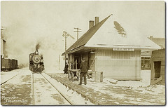 Monon Station, Chalmers, Indiana (Hoosier Recollections) Tags: people usa snow signs man men history industry station sepia buildings advertising awning clothing workmen hats indiana trains streetscene machinery transportation shops depot storefronts businesses railroads chalmers whitecounty realphoto hoosierrecollections
