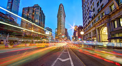 F.L.A.T (Tony Shi.) Tags: street nyc newyorkcity light urban panorama motion building classic night speed movement iron long exposure traffic flat time manhattan trails tourist planning transportation intersection   flatiron hdr lapse attraction       engergy