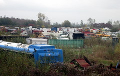 Junk Yard Near Buffalo, NY. (dccradio) Tags: railroad blue trees sky bus tree buses dumpster train truck cloudy centro rail overcast brush pole vehicles powerlines amtrak wires greenery trucks junkyard scrapyard utilitypole powerpole trashbin electricpole citybus electriclines salvageyard junktruck garbagecontainer railfans retiredcitybuses