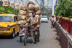 A loaded Rikscha crossing Howrah bridge in Kolkata, India. (cookiesound) Tags: life bridge people india man crossing taxi kolkata indien calcutta westbengal howrahbridge howrah rikscha rikschadriver loadedrikscha pushingrikscha fullyloadedrikscha