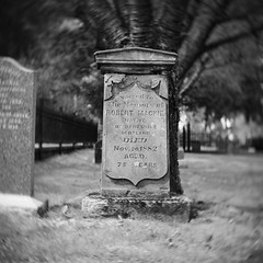 Rest in peace, Mister Mackie. (Eric Flexyourhead) Tags: old bw canada blur cemetery grave graveyard blackwhite bc bokeh britishcolumbia headstone 11 66 vignette langley fortlangley gravemarker ftlangley olympusem5 slrmagic26mmf14toylens