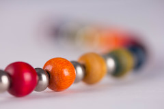 Between Us (explored 25/2/2017) (lacygentlywaftingcurtains) Tags: macro closeup rainbow woodenbeads necklace lgbt gay lesbian bracelet jewelry round shiny bright colourful colours bokeh pretty sooc macromondays thespaceinbetween