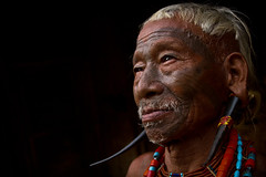 Konyak head-hunter. Mon district, Nagaland. NE India (NeSlaB .) Tags: naga nationalgeographic nagaland mon tribe tribal tattoo last warrior face portrait reportage dark look lowlight ethnies ethnography ethnology ethnic eyes photo photojournalism poverty asia canon culture developingcountries neslab man old society travel traditional headhunter world india indian neindia konyak airstyle headhunters davidecomelli earrings earlobe horn white black colors colorful country coiffure ornaments decorations piercing