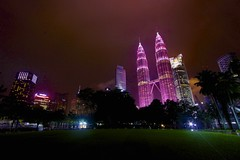 Pink KLCC from the Park (AryaPM23) Tags: park pink light sky beautiful beauty rain skyline night lights colorful pretty breast bright crowd petronas cancer silhouettes illuminated malaysia twintowers fountains awareness pinksky breastcancer klcc twoers vision:night=0844