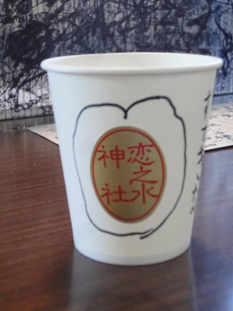 恋の水を入れるためのコップ(紙コップに神社のシールが貼って。|恋の水神社