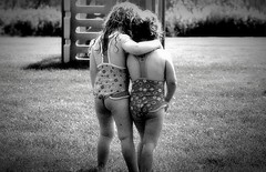 Cheeky (Myristica) Tags: girls summer blackandwhite bw black grass alaska kids sisters yard hair blackwhite hug sprinkler chubby wedgie bathingsuits blackandwhitephotography