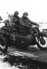 German motorcycle troops ride in a BMW R-12 with sidecar. Note the oilcloth dusters worn by the troops. The dusters were alternatively made of rubberized leather and were ankle length.