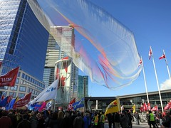 Colourful protest (Ruth and Dave) Tags: sky sculpture art net vancouver rainbow colours waterfront union rally protest floating flags canadaplace protesters truckers vancouverconventioncentre ted2014 skiespaintedwithunnumberedsparks janetechelmann