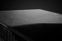 Legal Pad (Skuggzi) Tags: city uk shadow england urban blackandwhite bw abstract building london window monochrome lines architecture modern contrast dark grid office europe noir moody unitedkingdom outdoor dramatic minimal lookingup lookup diagonal highrise gb slats groove docklands sunlit louvres towerhamlets