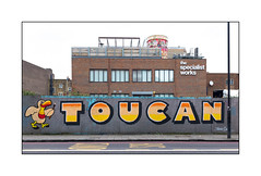 Sign Writers/Muralists (Toucan Signs), North London, England. (Joseph O'Malley64) Tags: toucansigns signwriters northlondon london england uk britain british greatbritain art artists artistry artwork mural muralists hordings chipboardpanels fencing buildings brickwork bricksmortar pointing windows roofgarden signs signage satellitedish lamppost accesscovers pavement granitekerbing tarmac redroute nostoppingatanytime busstand buslane dividingline urban urbanlandscape aerosol cans spray paint fujix accuracyprecision