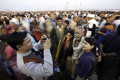Kumbh Memories (Apratim Saha) Tags: carnival red portrait people woman sun india man motion water yellow horizontal shirt scarf river gold golden ray sitting hand adult indian group festivals culture ring holy gathering bathe nectar spiritual devotees dip m