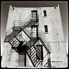 The Escape Route (Stella Blu) Tags: canada monochrome stairs blackwhite alberta squareformat fireescape lightshadow stellablu fortmacleod americanhotel 15challengeswinner favescontestwinner nikond300 thechallengefactory tokina1116 agcgwinner herowinner storybookwinner pregamewinner favescontestfavored