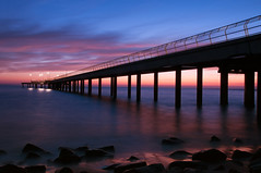 Early morning by the pier (Pat Charles) Tags: ocean longexposure sea reflection beach water clouds dawn pier nikon rocks jetty australia 1001nights flickraward 1001nightsmagiccity flickraward5 flickrawardgallery